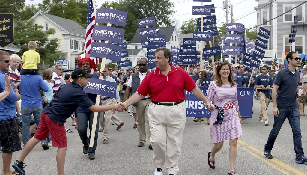 Republican presidential candidate New Jersey Gov. Chris Christie shakes hands as he walks in a Fourth of July parade with his wife wife Mary Pat in Wolfeboro, N.H. (AP Photo)