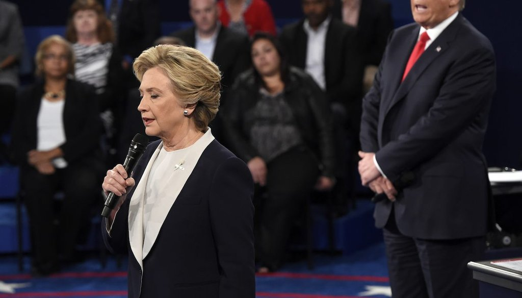 Democratic presidential nominee Hillary Clinton, left, talks as Republican presidential nominee Donald Trump watches her during the second presidential debate at Washington University in St. Louis, Sunday, Oct. 9, 2016. (Saul Loeb/Pool via AP)