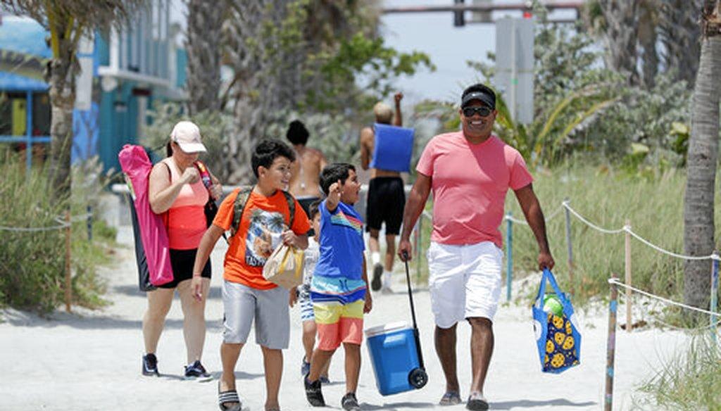 A family walks through an entrance to Cocoa Beach, Fla., Thursday, April 23, 2020. (AP)