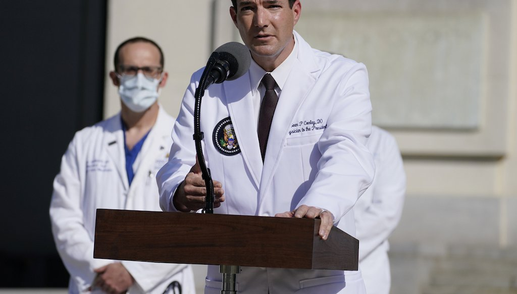 Dr. Sean Conley, physician to President Donald Trump, talks with reporters at Walter Reed National Military Medical Center. (AP Photo/Evan Vucci)