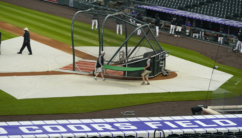 Grounds crew workers prepare to pull the tarpaulin as a light rain descends on Coors Field in Denver on April 6, 2021. Major League Baseball decided to move its 2021 All-Star Game to Denver from Atlanta as a result of changes in Georgia's voting law. (AP)
