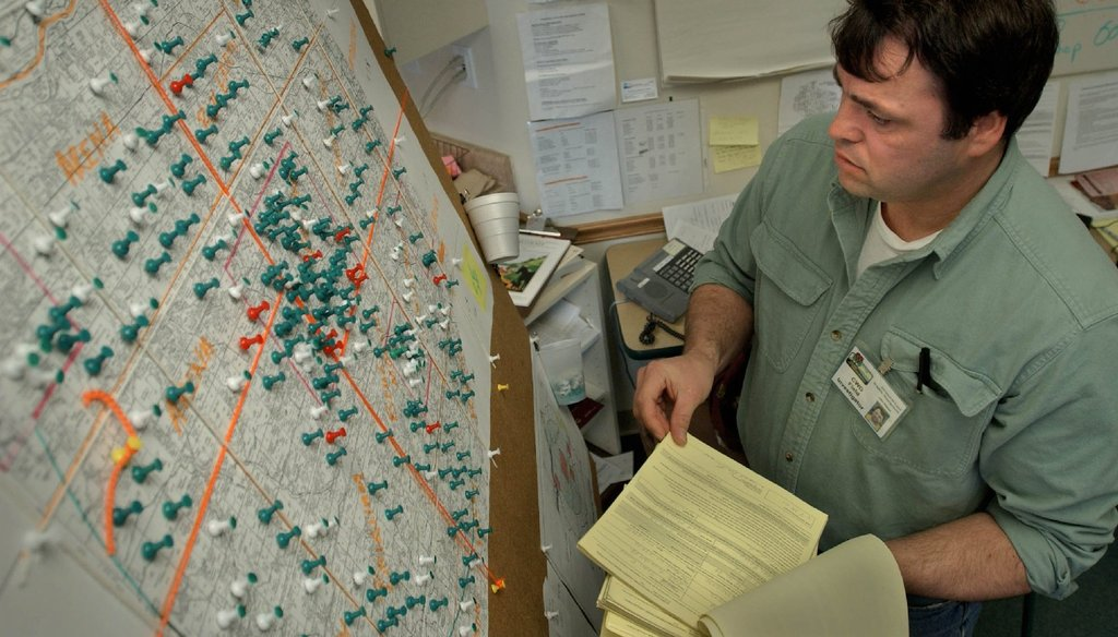 John Nielsen, a DNR wildlife biologist, consults a map containing an area to record where deer collecting permits have been issued in 2002. (Milwaukee Journal Sentinel)