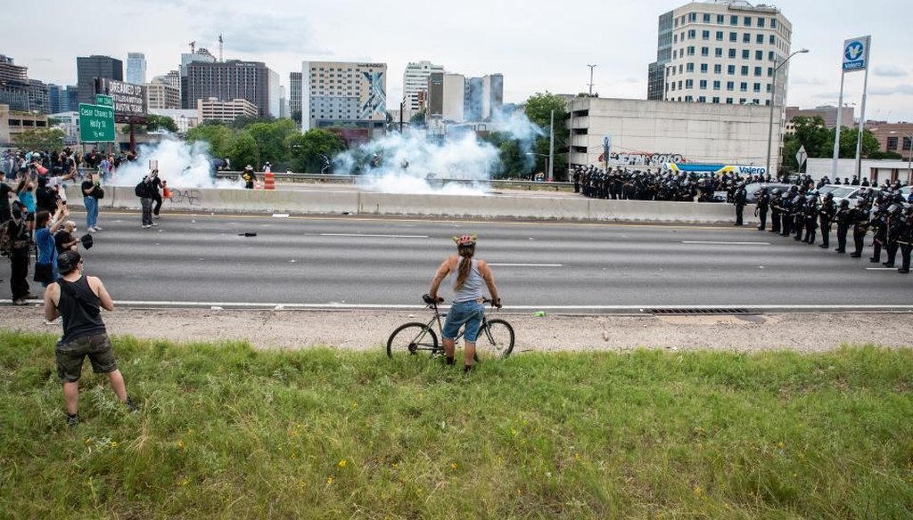 A protester watches as tear gas is used to clear out I35 during a protest in Austin, Texas on May 31. (Sergio Flores for AMERICAN-STATESMAN)