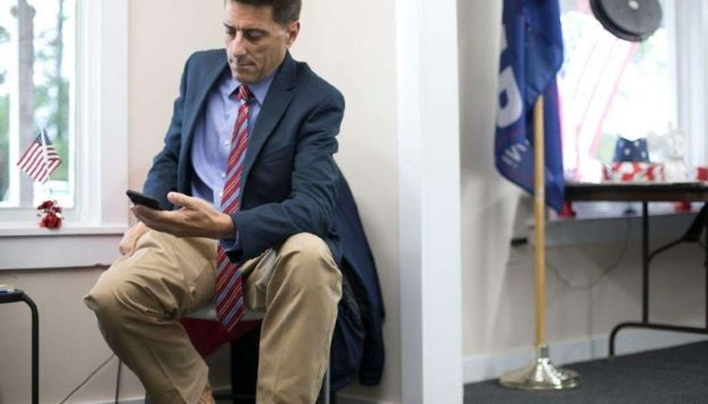 Dallas Woodhouse, the executive director of the North Carolina Republican Party, checks his phone as he prepares for a press conference on Monday, October 16, 2017, at the Orange County Republican headquarters in Hillsborough, N.C.