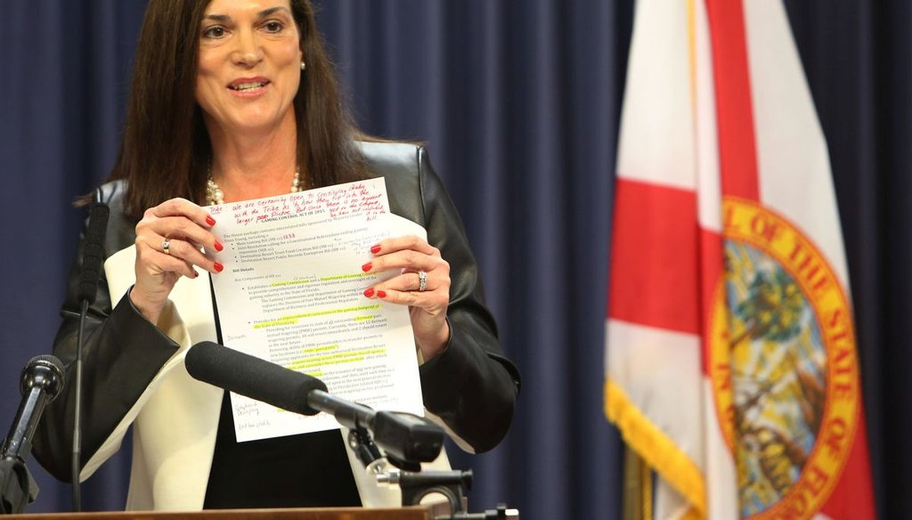 Rep. Dana Young, R- Tampa, shows a copy of her gaming bill to members of the media.