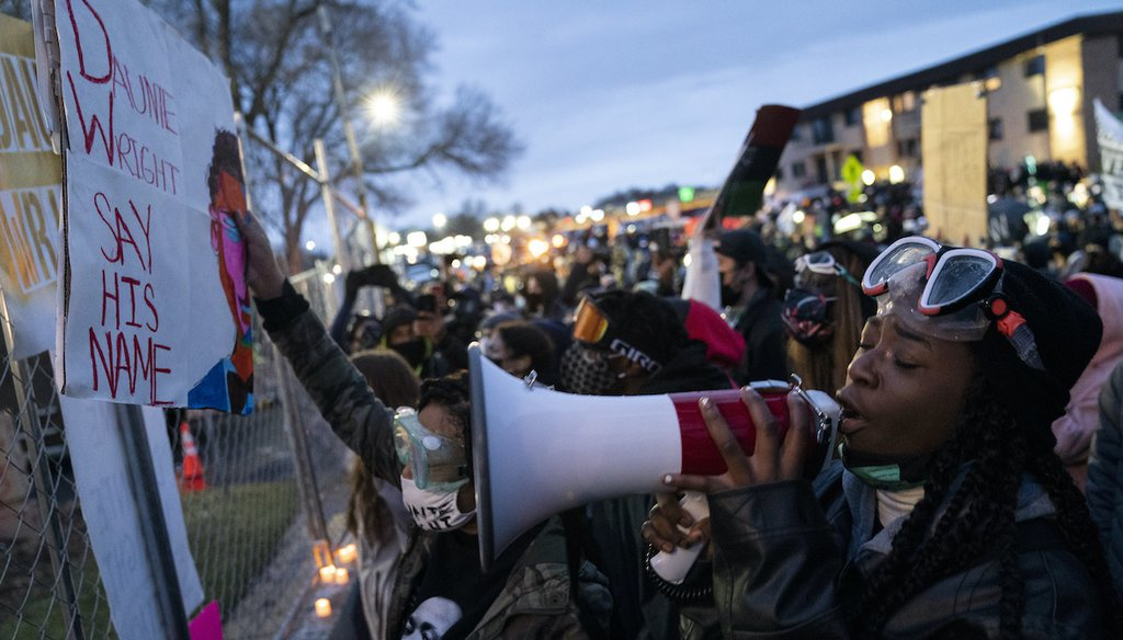 Demonstrators gather along a perimeter fence during a protest over Sunday's fatal shooting of Daunte Wright during a traffic stop, outside the Brooklyn Center Police Department on Wednesday, April 14, 2021, in Brooklyn Center, Minn.