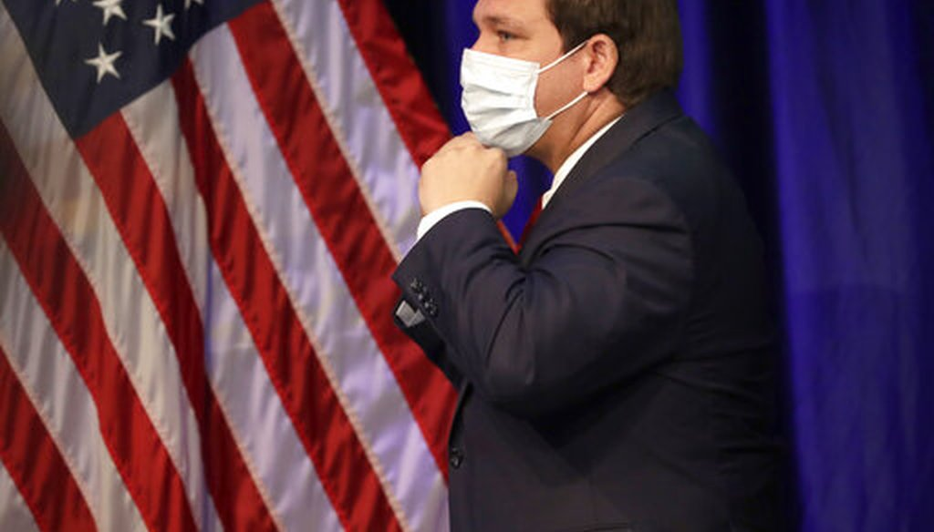 Florida Gov. Ron DeSantis puts on his mask to protect against the new coronavirus as he leaves a news conference on COVID-19, Friday, June 19, 2020, at Florida International University in Miami. (AP)