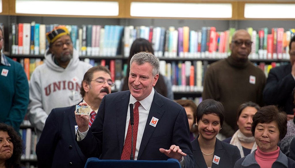 New York City Mayor Bill de Blasio holds a municipal identification card. (Courtesy: New York City Mayor's Office)