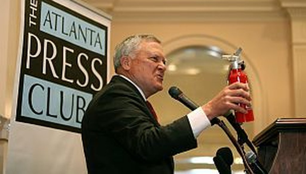 """Georgia Gov. Nathan Deal brings out his fire extinguisher during his speech at the Atlanta Press Club on April 30, 2013. The governor was prepared to put out the flames of any """"Pants on Fire"""" violator. (AJC photo/Jason Getz)"""