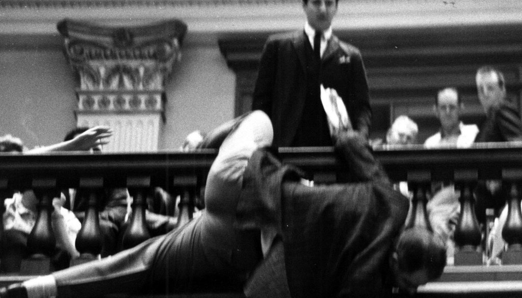 During a 1964 speech on re-apportionment, Rep. Denmark Groover, D-Macon, nearly fell over the state House railing trying to adjust the hands of the clock to keep it from reaching midnight. File photo by Joe McTyre / AJC