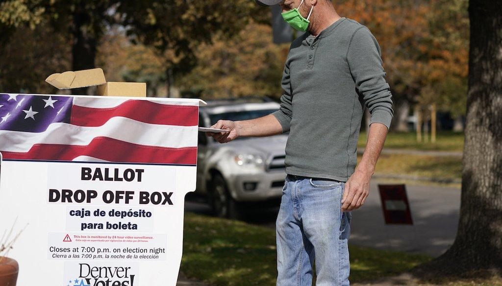 A voter casts a ballot in a dropbox Nov. 3, 2020, in Denver. (AP Photo/David Zalubowski)