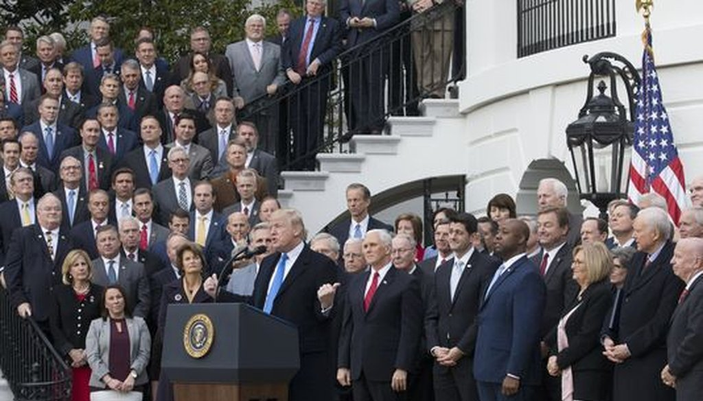 President Donald Trump and Republican lawmakers celebrated passage of the GOP tax reform bill at a White House event on Dec. 20, 2017. Does it mean $1,000 or more per year for individuals? (EPA-EFE)