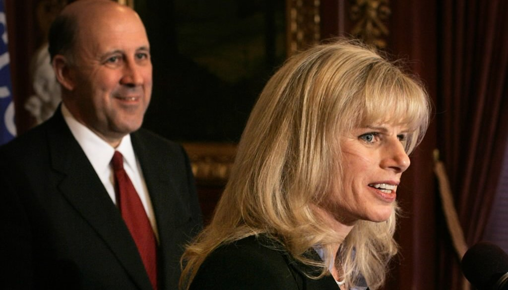 Mary Burke speaks to the media on Jan. 25, 2005, after then-Gov. Jim Doyle (background) announced he had named her his commerce secretary.