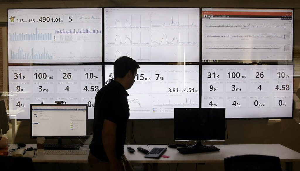 In this 2015 photo, an employee in the of DraftKings, a daily fantasy sports company, walks past screens displaying the company's online system stats in Boston. (Associated Press)