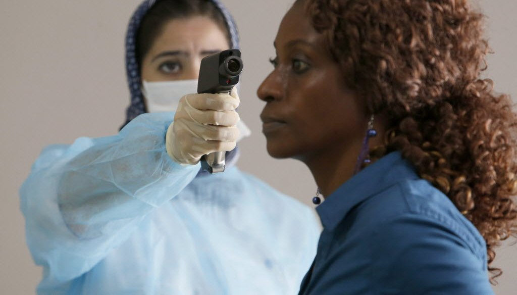 A Moroccan health worker uses a thermometer to screen a passenger at the arrivals hall of the Mohammed V airport in Casablanca on Oct. 9, 2014. Ebola has killed more than 4,500 people in West Africa. (AP photo)