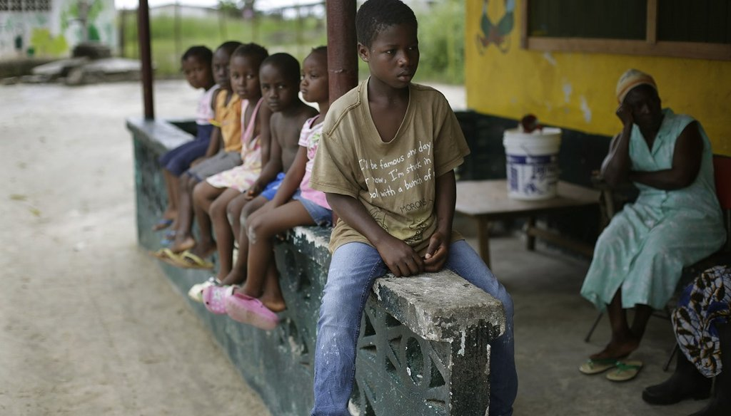 Children sit at a bench in an orphanage in Liberia. (AP Photo)