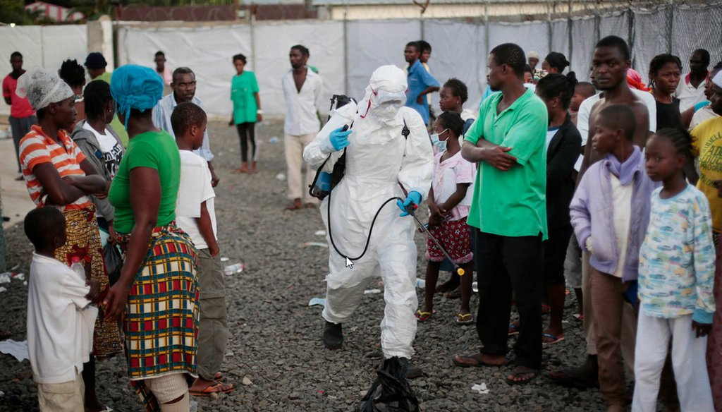 A medical worker sprays people being discharged from the Island Clinic Ebola treatment center in Monrovia, Liberia. (AP Photo/Jerome Delay)