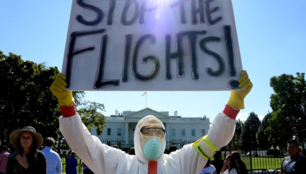 A protester stands outside the White House asking President Barack Obama to ban flights in an effort to stop Ebola on Oct. 17, 2014.