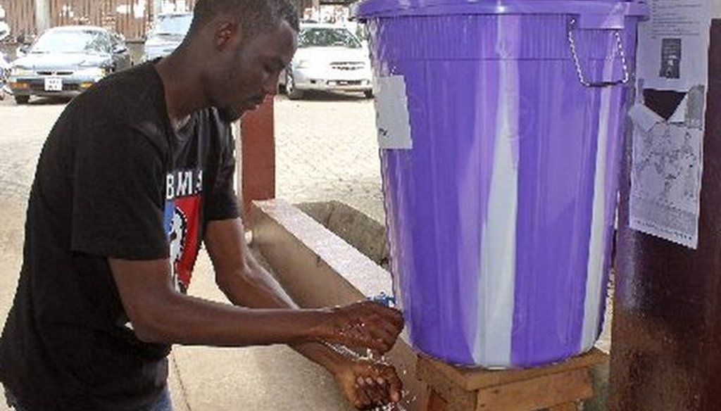 A man in Freetown, Sierra Leone, washes his hands with disinfectant to prevent Ebola infection before entering a hospital on July 15, 2014. An Ebola outbreak in Liberia and Sierra Leone is ongoing.