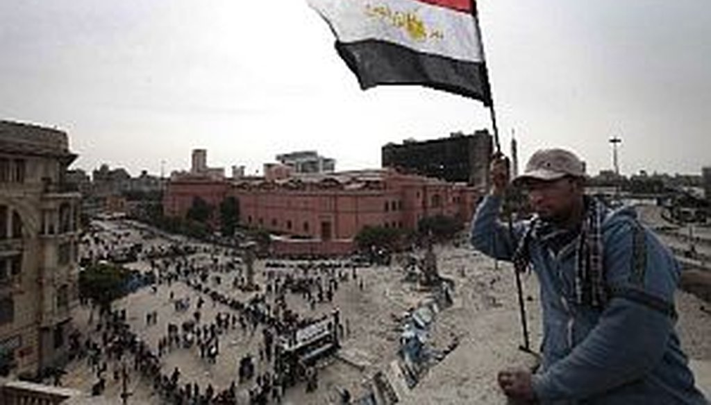 An anti-government protester waves an Egyptian flag in Cairo on Friday