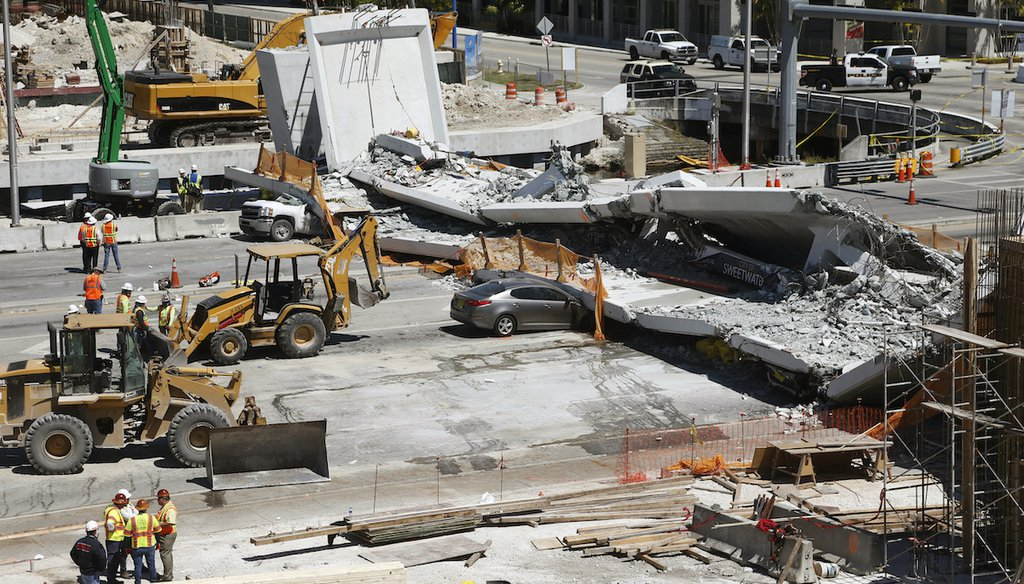 Crushed cars are shown under a section of a collapsed pedestrian bridge, Friday, March 16, 2018 near Florida International University in the Miami area. (AP)
