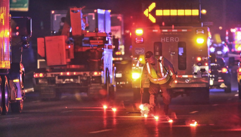 A DOT worker lays down flares at the scene of a fatal traffic crash in 2013 on I-85 in Gwinnett County. Photo by John Spink / AJC