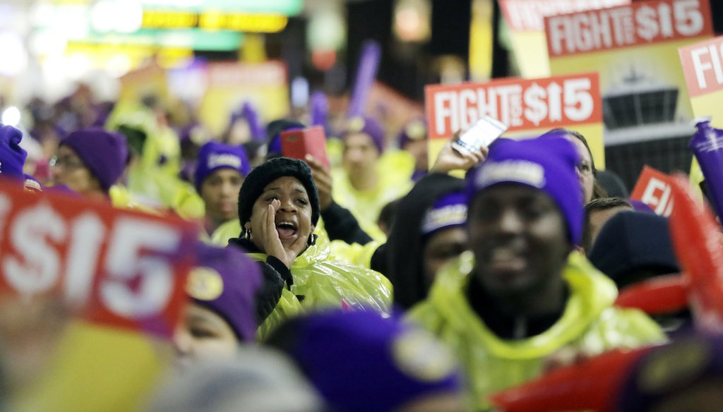 A woman shouts while marching with service workers asking for $15 minimum wage pay during a rally at Newark Liberty International Airport, Tuesday, Nov. 29, 2016, in Newark, N.J. The event was part of the National Day of Action to Fight for $15. (AP)