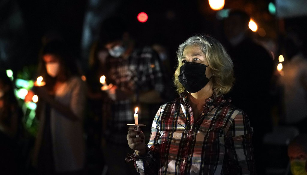 A woman wears a protective face mask while holding a candle during an outdoor Christmas Eve Service of Lights at the Granada Presbyterian Church, Thursday, Dec. 24, 2020, in Coral Gables, Fla. The service was held outdoors for COVID-19 safety. (AP)
