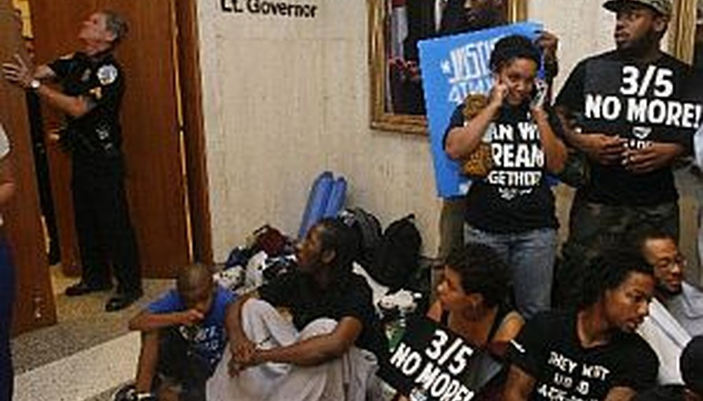 A police officer closes Florida Gov. Rick Scott's office at 5 p.m. on July 16, 2013, as protestors sit in the hallway at the Capitol in Tallahassee, Fla.