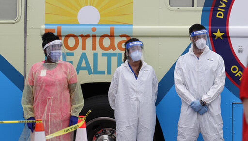Health care workers wear personal protective equipment as they stand in front of a mobile testing lab during a news conference at a COVID-19 testing site at Hard Rock Stadium, Wednesday, May 6, 2020, in Miami Gardens, Fla. (AP)
