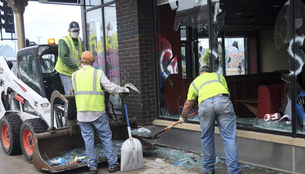 Workers clear broken glasses in front of a building near the Minneapolis Police Third Precinct after a night of rioting as protests continue over the arrest of George Floyd who died in police custody. (AP Photo/Jim Mone)