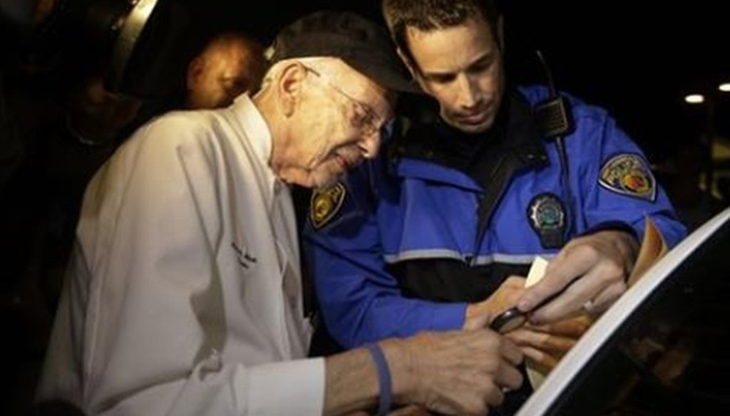 Arnold Abbott, 90, gets fingerprinted by police during his Nov. 5 arrest for violating the city's ordinance about rules for feeding the homeless outdoors. (AP)