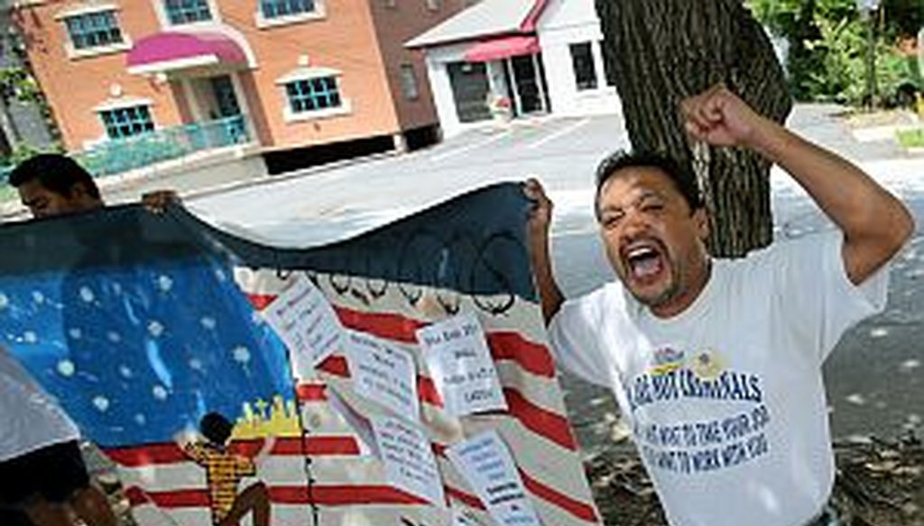 Thomas Martinez chants toward the Georgia GOP headquarters during a rally July 9, 2013. Participants were urging House GOP members to move forward on the Senate's immigration reform bill. (AJC Photo/Jason Getz)