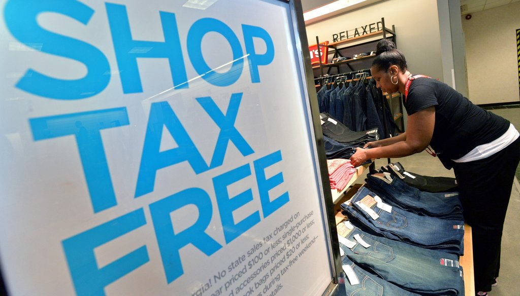 A worker arranges a display of clothing at JC Penney at Northlake Mall before the sales tax holiday in 2013. File photo by Hyosub Shin / AJC