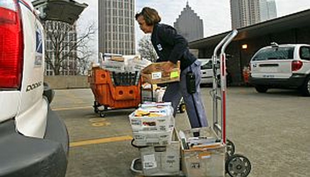 Mail carrier Annie Johnson gathers mail for her routes at the post office in midtown Atlanta.  The American Postal Workers Union says the Postal Service is funded through stamps and postage, and doesn't run on tax dollars. (AJC photo/Jason Getz)