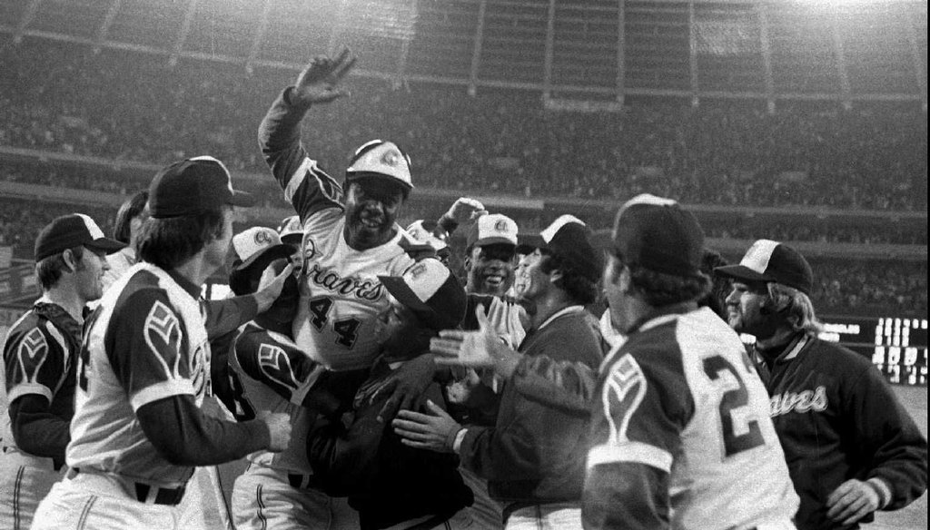 The Atlanta Braves congratulate Hank Aaron, top with hand raised, after his 715th career home run at Atlanta Fulton County Stadium on April 8, 1974. AP file photo.