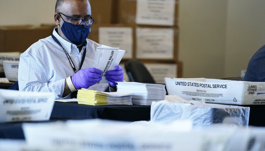 An election inspector looks at an absentee ballot as vote counting in the general election continues at State Farm Arena, Wednesday, Nov. 4, 2020, in Atlanta. (AP)