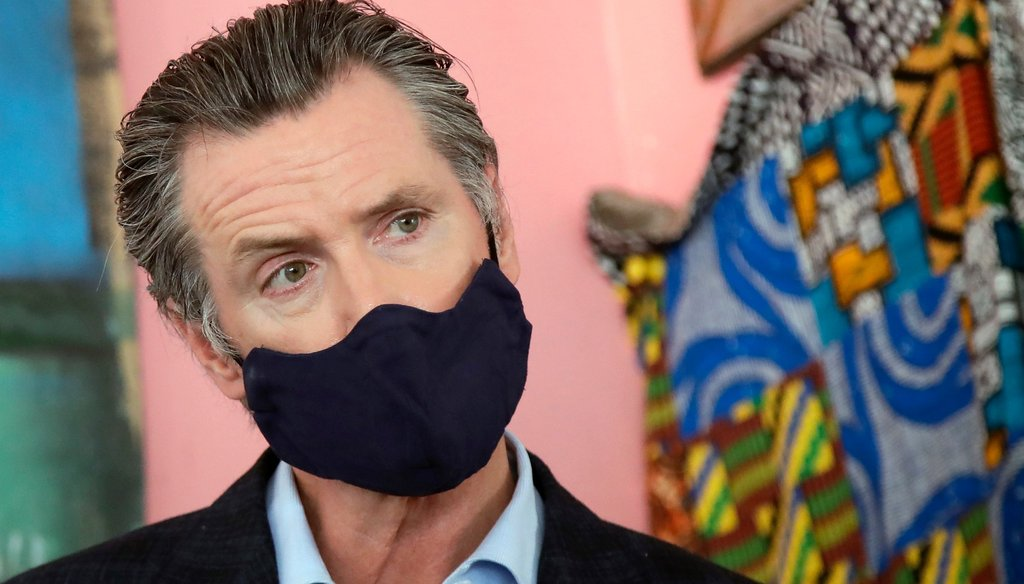 Gov. Gavin Newsom wears a protective mask on his face while speaking to reporters at a restaurant during the coronavirus outbreak in Oakland, Calif., Tuesday, June 9, 2020. AP Photo/Jeff Chiu