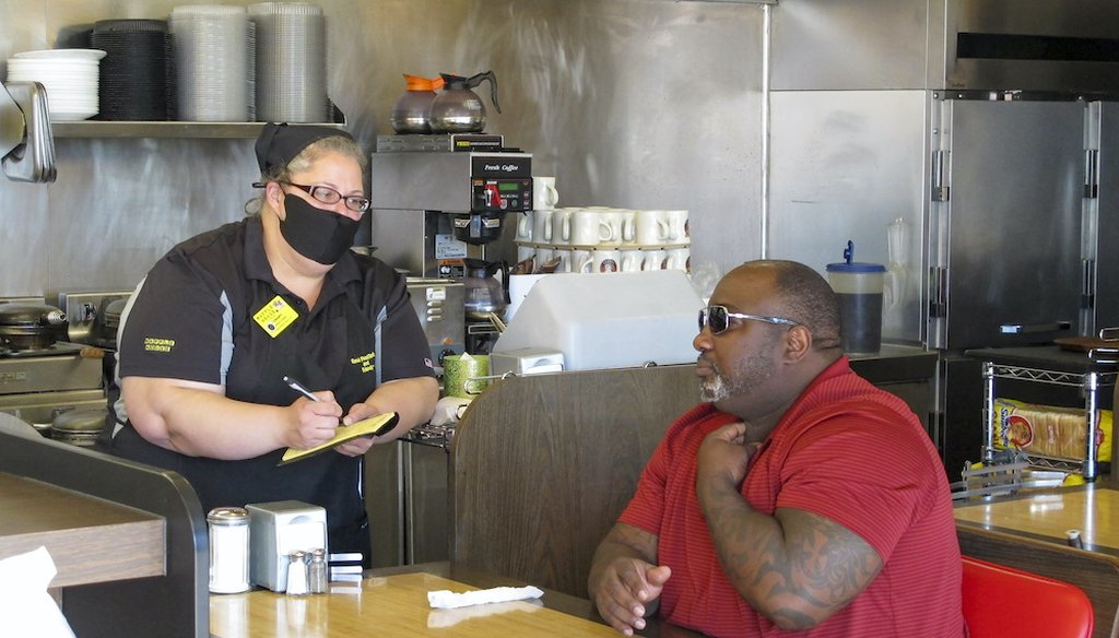 A customer orders food at a Waffle House restaurant in Savannah, Georgia, after restaurants statewide were allowed to resume dine-in service with restrictions. (AP Photo/Russ Bynum)