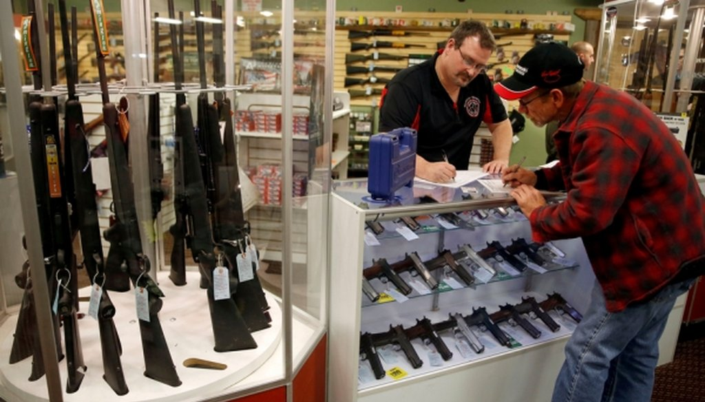 Steven King, left, fills out paperwork before selling a handgun to first-time gun owner Dave Benne at Metro Shooting Supplies, in Bridgeton, Mo., in 2014. (AP/Jeff Roberson)