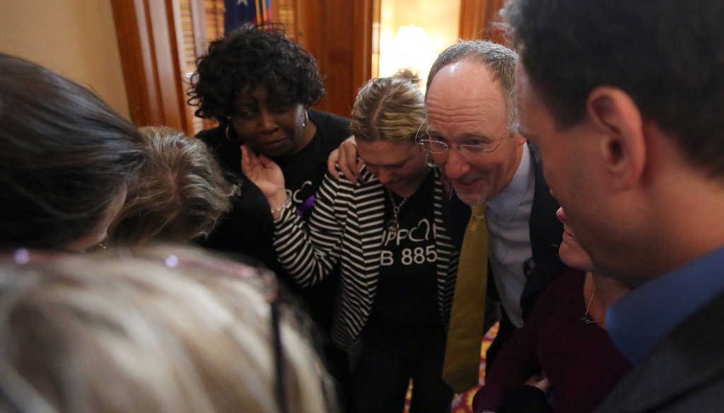 Georgia state Rep. Allen Peake, R-Macon, and supporters of his legislation to provide a form of medical marijuana to seizure patients, huddle after the bill passes one chamber of the state Legislature. Photo Credit: Ben Gray/AJC.