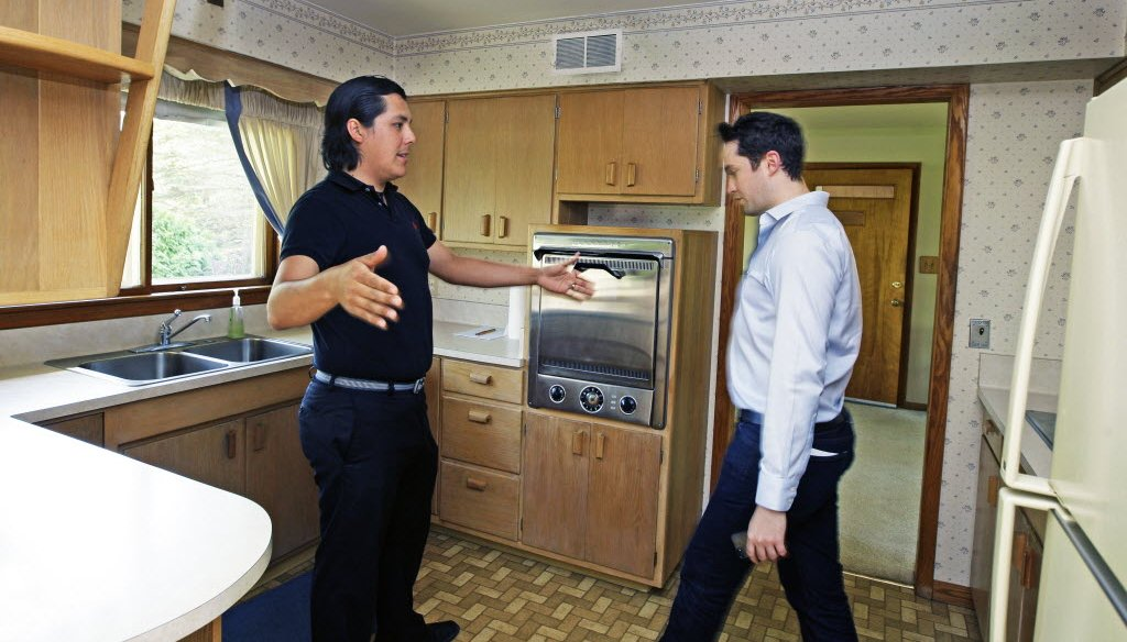 David Gonzalez, left, talks about changes he would make to the kitchen while looking at this 1950's suburban Milwaukee home for sale with real estate agent Wil Poull, right, in May 2013.