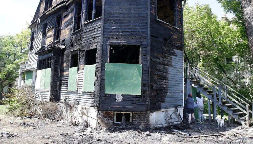Neighbors collect remnants from outside a home that was burned June 23, 2020, during civil unrest. The duplex was again set on fire the following day, June 24, 2020. (Rick Wood/Milwaukee Journal Sentinel