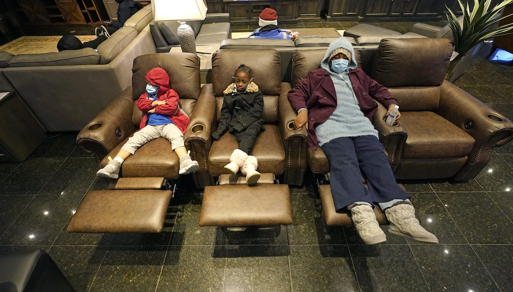 Joecyah Heath, left, Morning Day, center, and Jenesis Heath rest in recliners at a Gallery Furniture store which opened as a shelter Wednesday, Feb. 17, 2021, in Houston. (AP)