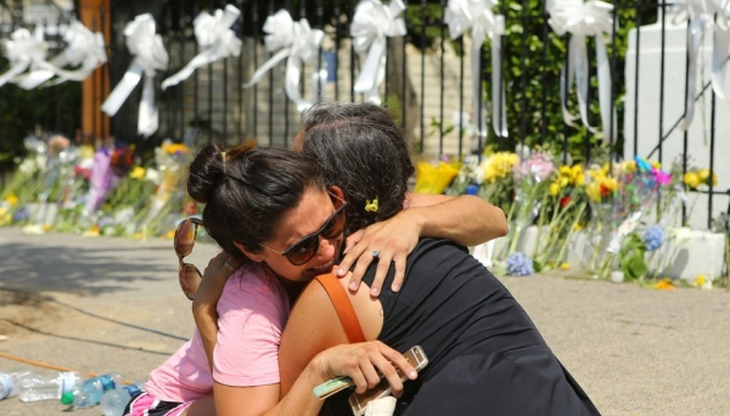 "Stewart Watson, right, comforts Maranda Mincey at the sidewalk memorial at the ""Mother"" Emanuel A.M.E. Church in Charleston, S.C., on June 19, 2015. A gunman killed nine worshippers there the previous day. (Curtis Compton/Atlanta Journal-Constitution/TNS)"