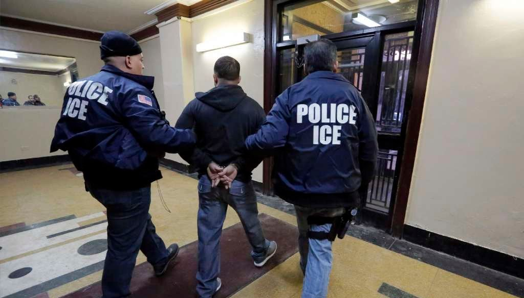 Immigration and Customs Enforcement officers escort an arrestee in an apartment building in the Bronx on March 3, 2015, during a series of early-morning raids. (AP/Richard Drew)