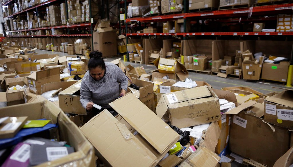 An employee sorts through boxes at the Win.It America warehouse in Walton, Ky., on May 1, 2018. After an ICE agent arrested one of the company's employees, the warehouse lost 28 workers over several weeks and struggled to meet its shipping deadline. (AP)