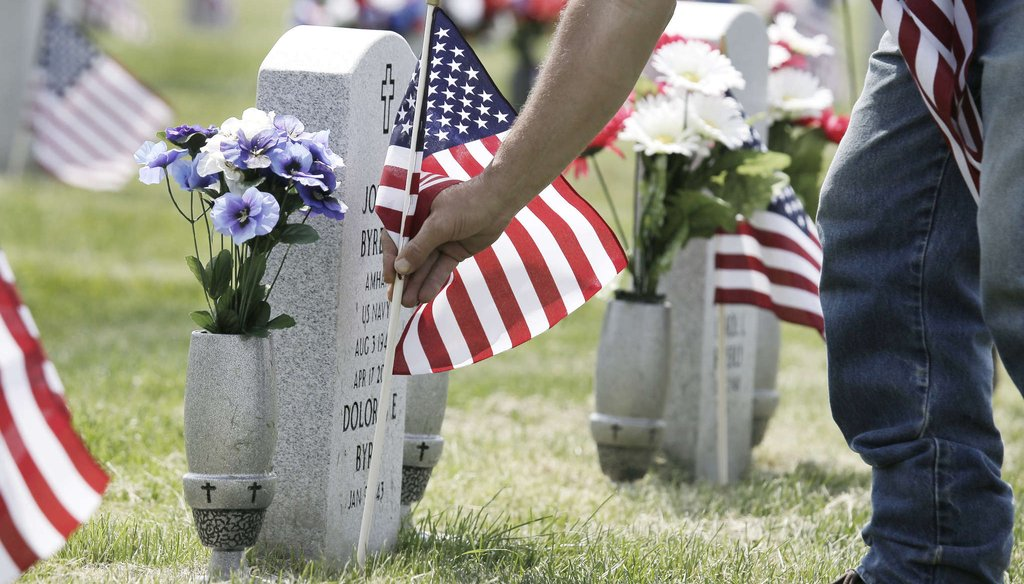 An employee at Gloucester County Veterans Memorial Cemetery in Monroe Township replaces a broken American flag on a veteran's grave. ELIZABETH ROBERTSON / Inquirer Staff Photographer