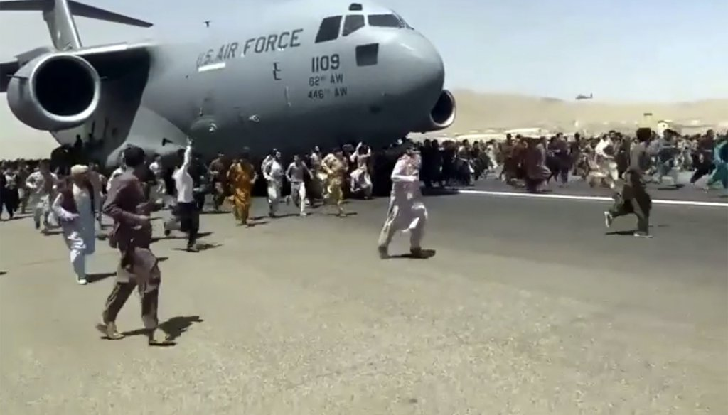 In this Aug. 16, 2021 photo, hundreds of people run alongside a moving U.S. Air Force C-17 transport plane at the Kabul, Afghanistan, international airport. A similar image taken at the scene is being falsely characterized in some social media posts. (AP)