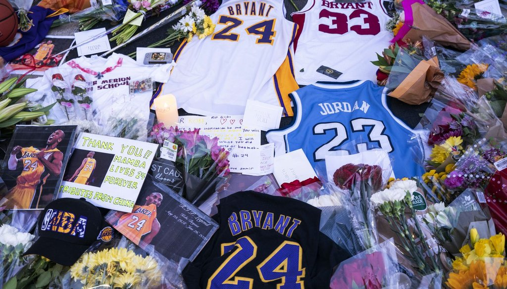Flowers, jerseys and imagery are left in remembrance to Kobe Bryant at a small memorial at the entrance of the Bryant Gymnasium at Lower Merion High School, Monday, in Wynnewood, Pa. (AP)